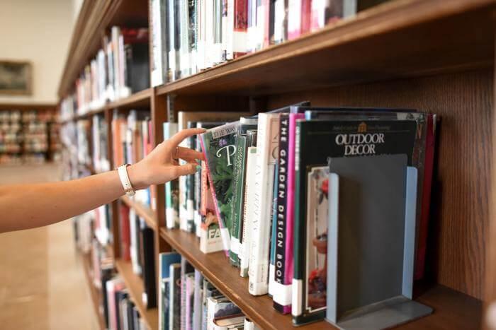 図書館で本を手に取る
